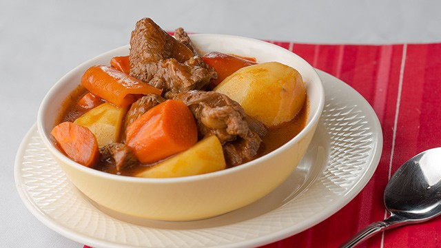 beef mechado in a bowl over a white plate