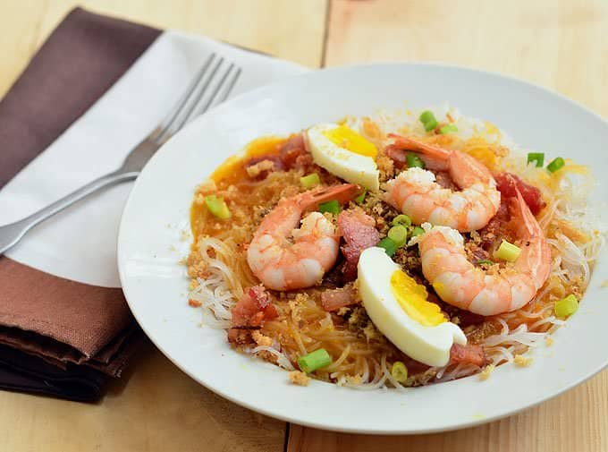 palabok on a white plate top with shrimp and egg
