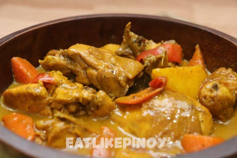 filipino chicken curry with red bell pepper tomatoes and carrots in a bowl