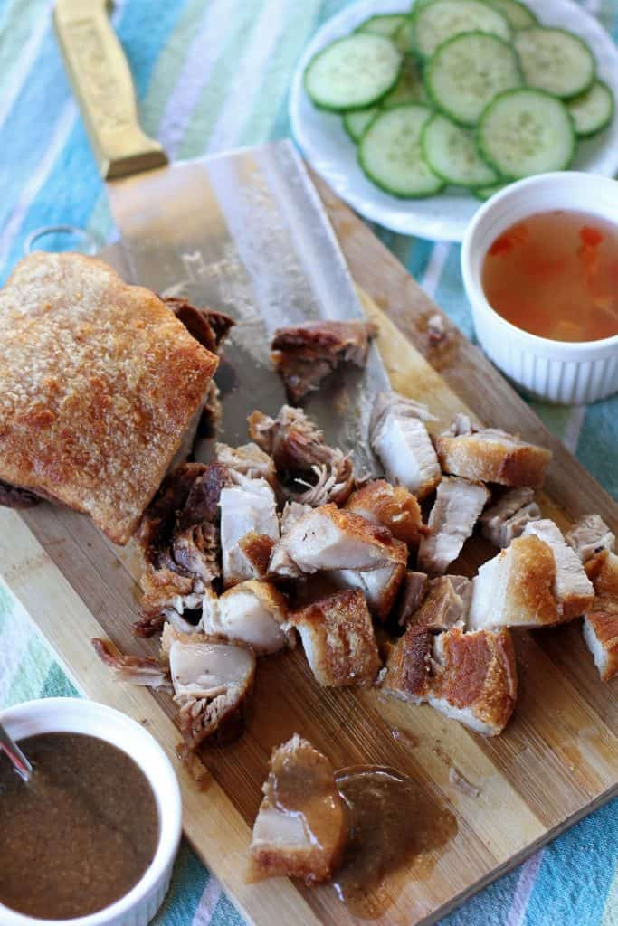 crispy lechon kawali over chopping board with knife, sauce, vinegar and cucumber