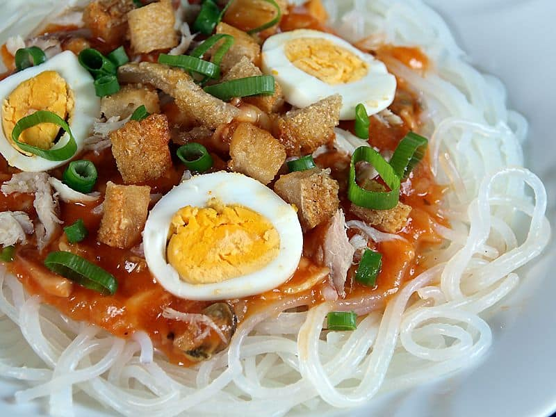 palabok top with chicharon, spring onions, and sliced eggs.