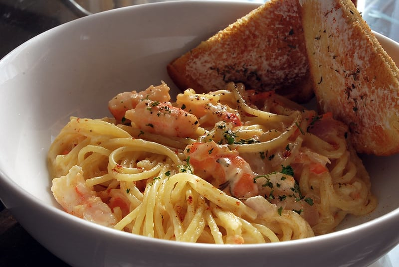 alfredo with shrimp in a white bowl with toasted bread on side
