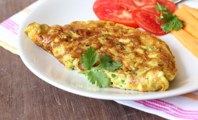 vegetable omelette on a plate with sliced tomatoes