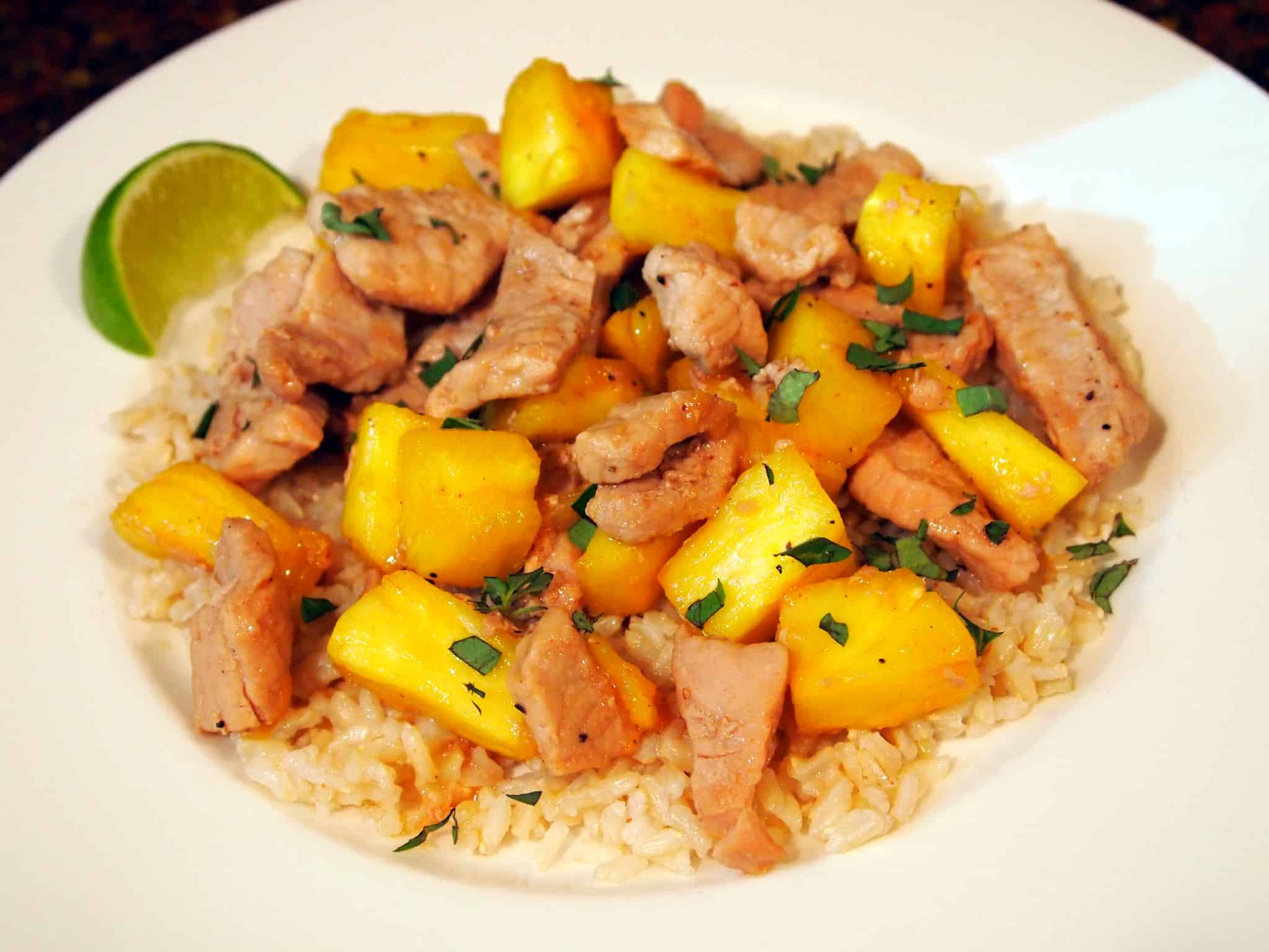pineapple pork stir fry on a plate with rice and lime