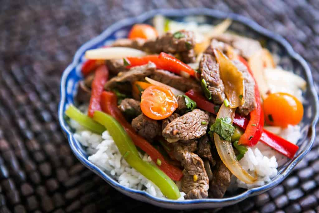 Stir fry pepper steak with rice in a porcelain bowl