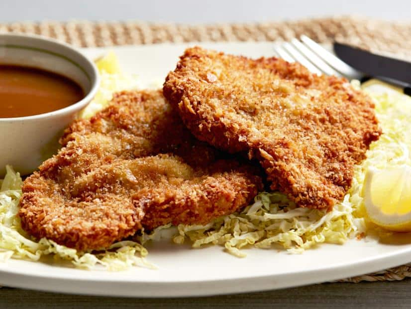 pork tonkatsu with shredded cabbages on a plate with sauce and sliced lemon