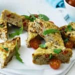 tuna frittata on a plate with baby tomatoes