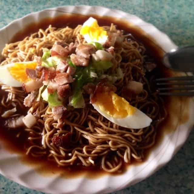 pancit cabagan on a white bowl with slices of egg on top