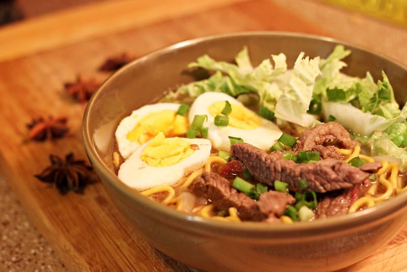 beef mami in a brown bowl placed on a wooden board