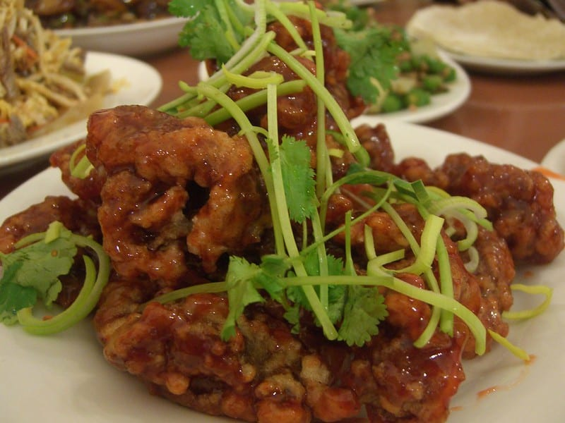 crispy sweet and sour pork on a plate top with fresh herbs