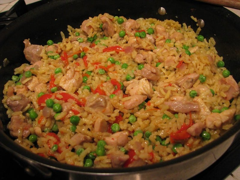chicken paella in a large black bowl