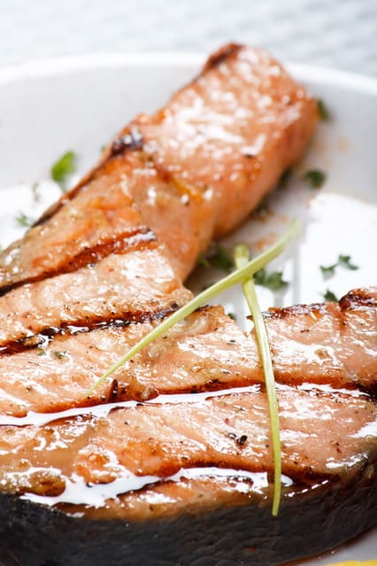 salmon steak sprinkle with herbs on a plate