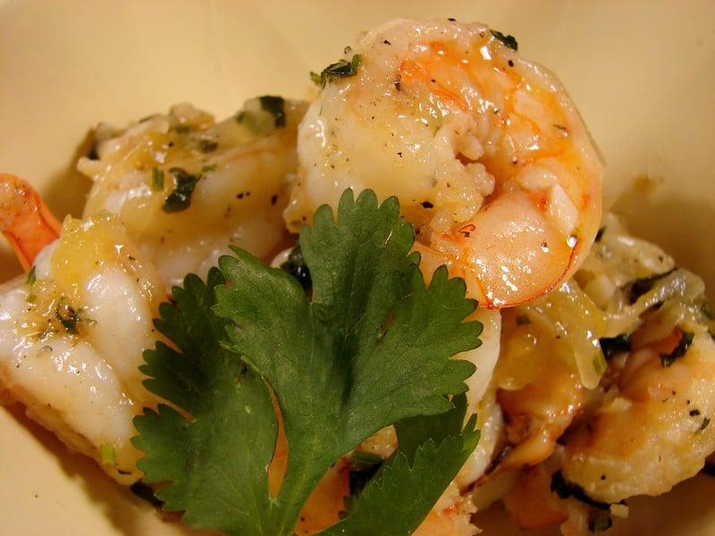 mango shrimp in a bowl with oregano on top