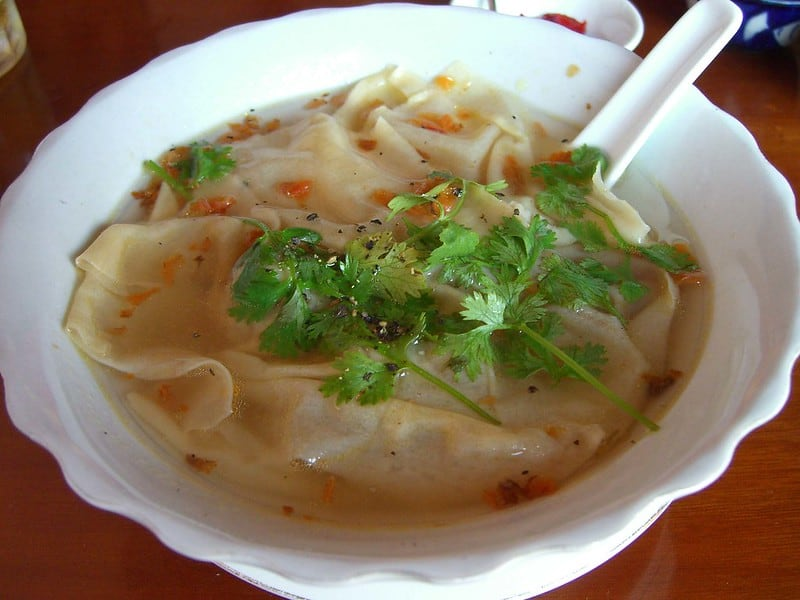 wonton soup in a bowl with parsley on top.