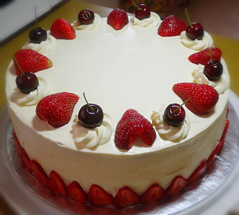 strawberry cheesecake with cherries and strawberries on top