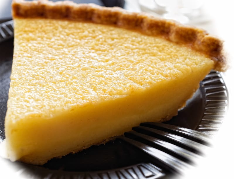 a slice of buttermilk pie on a silver plate