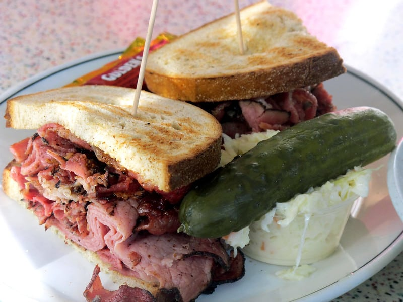 pastrami sandwich on a plate with whole pickle on the side