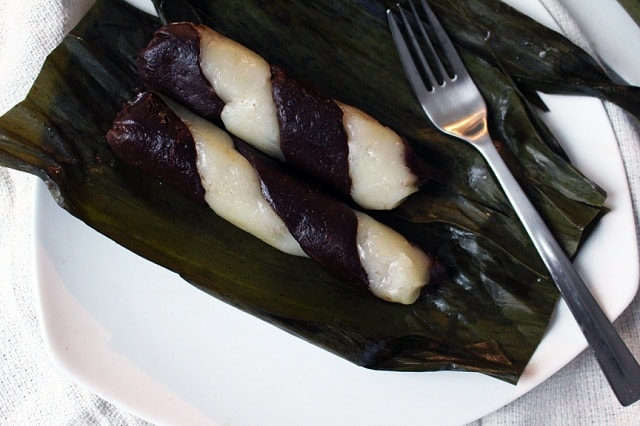 suman moron on a white plate placed on banana leaf with fork