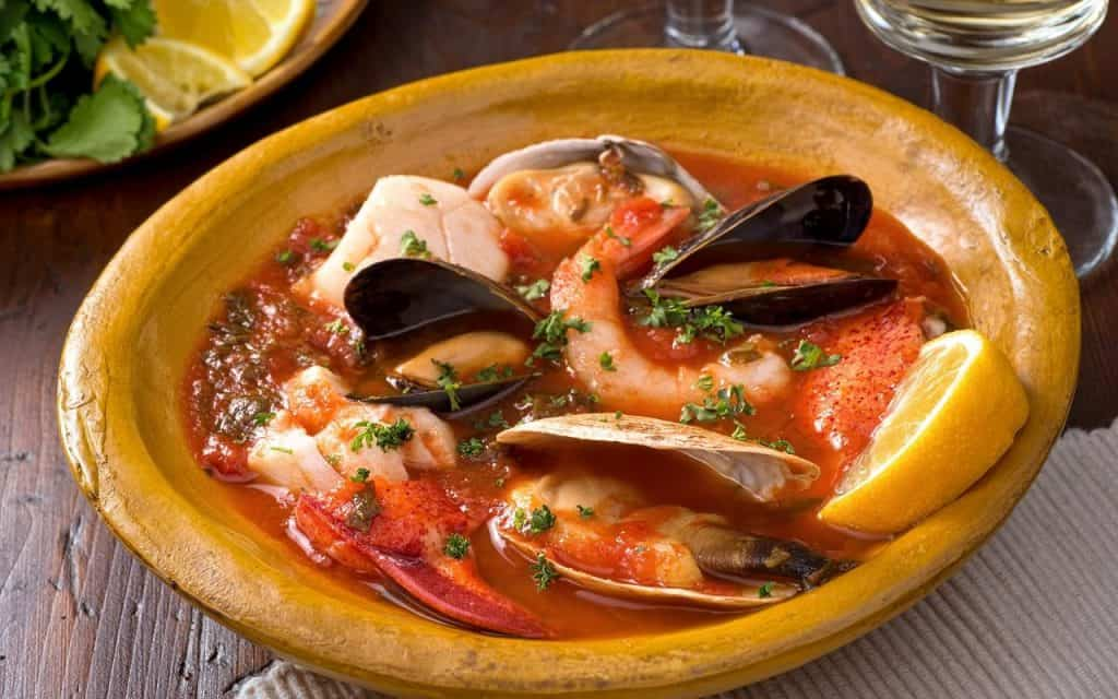 cioppino with sliced lemon in a bowl