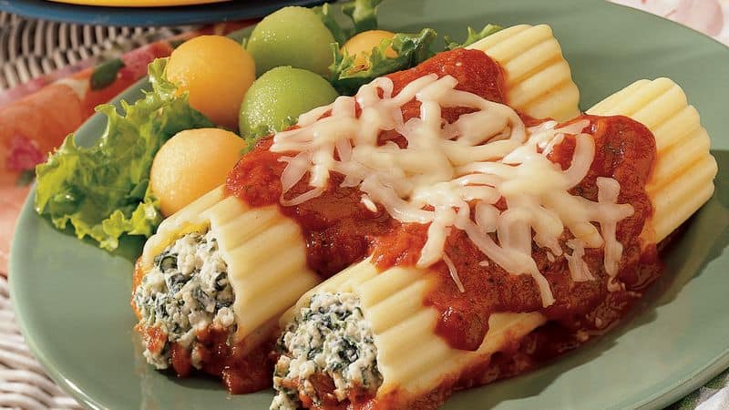 manicotti in a green plate with red sauce and cheese on top