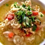 chicken noodle soup in a bowl top with herbs