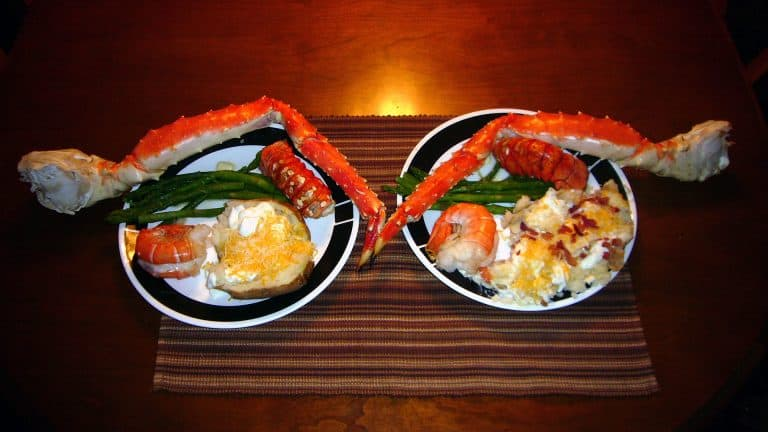 baked king crab leg on a plate with sides