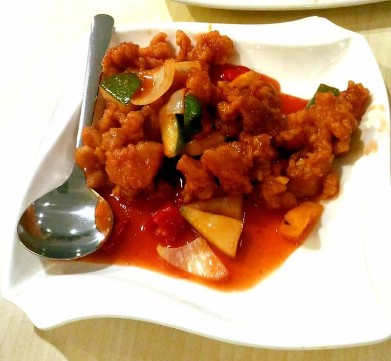 sweet and sour chicken on a plate with spoon