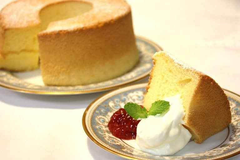 vanilla chiffon cake on a plate with icing on side